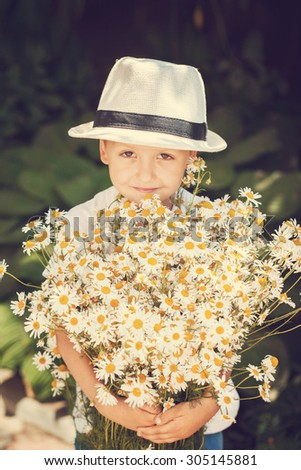 Portrait little boy in a hat with big white bouquet of chamomiles. Summertime. Toning image - stock photo