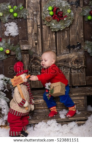 Portrait little girl in a knitted red sweater. Cute baby sitting in christmas decorations.The child opens a gift