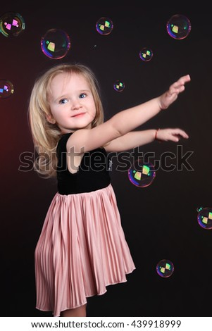Portrait little girl in motion plays with soap bubbles. On black background in the studio - stock photo