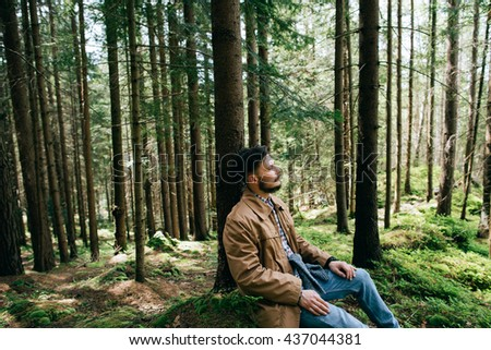 Portrait lonely bearded man hipster sits dream in mountain green forest