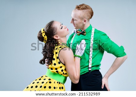 Portrait lovely funny dancer couple dressed in boogie-woogie rock'n'roll pin up style posing together in studio. Woman in yellow polka dots dress and man in green shirt.  - stock photo