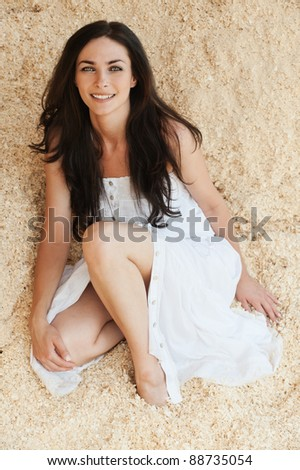 portrait lovely young woman sitting sand bare feet wearing white dress - stock photo