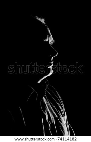 Portrait (low key, face outline) of a Caucasian man  - black and white. - stock photo