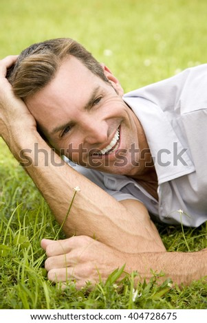 portrait man lying on grass leaning on elbow - stock photo