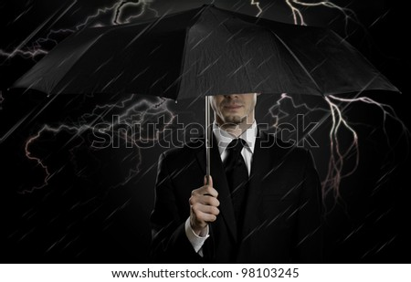 portrait  man the  beautiful  man in black costume with blak umbrella,  special-service agent or  guard - stock photo
