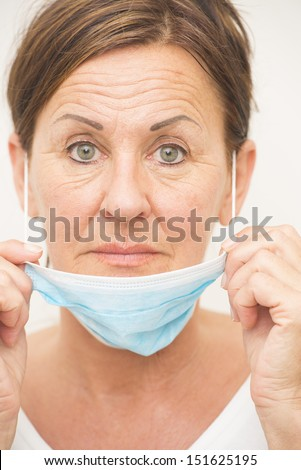 Portrait mature woman nurse or doctor, medical professional with mask and serious facial expression isolated on white background.