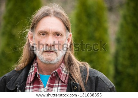 Portrait middle aged man with long hair, beard, and mustache - stock photo