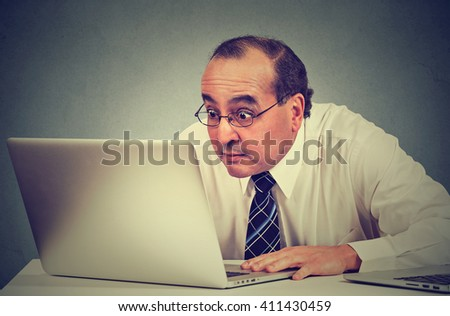 Portrait middle aged shocked business man sitting in front of laptop computer looking at screen isolated on gray wall background. Funny face expression emotion feelings problem perception reaction