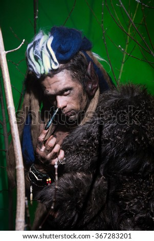 Portrait muscular werewolf with dreadlocks with long nails among the branches of the tree. Gothic image of scary diabolical creatures for Halloween - stock photo