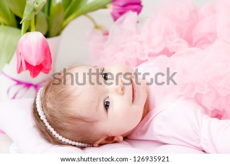 Portrait od adorable  infant girl in a pink petty with bouquet of tulips