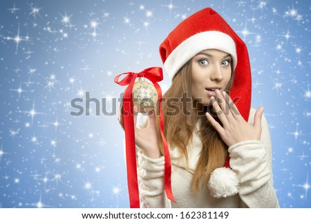 portrait od girl with santa claus hat and warm sweater taking bauble in the hand and looking in camera with surprised expression. in blue sky background.