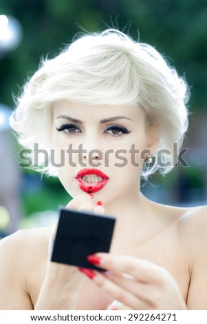 Portrait od pretty young sexy blonde lady with red nails put on lipstick holding small mirror standing on natural background closeup, vertical picture - stock photo