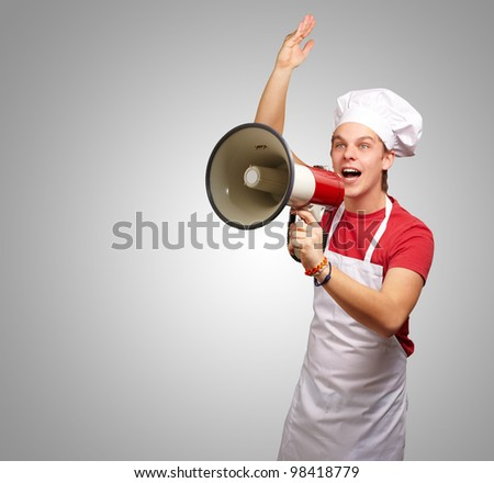 portrait of a a cook shouting with a megaphone against a grey background