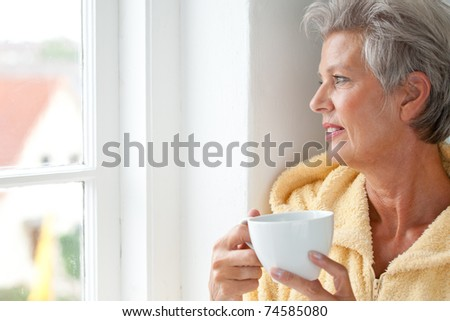 Portrait of a active senior woman with cup - stock photo