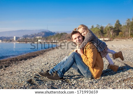 Portrait of a adorable girl hugging his young father at the beach - stock photo