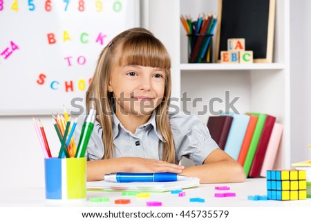 Portrait of a adorable little girl in school at the desk - stock photo
