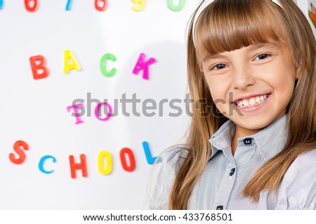 Portrait of a adorable little girl in school in front of whiteboard. Back to school. - stock photo