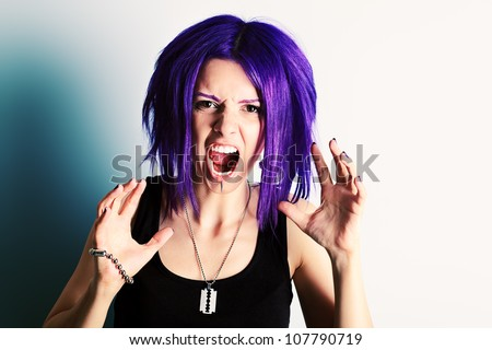 Portrait of a aggressive punk girl with purple hair.