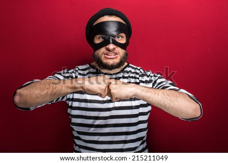 Portrait of a angry bandit threaten with fist on red background  - stock photo