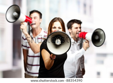 portrait of a angry  group of employees shouting using megaphones against a city background - stock photo