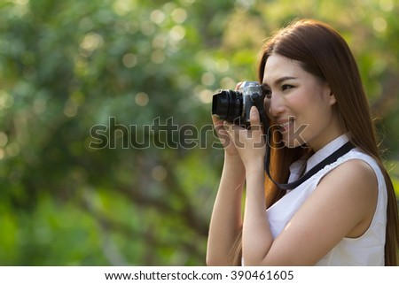 portrait of a asian beautiful girl with a camera taking photos in a garden - stock photo