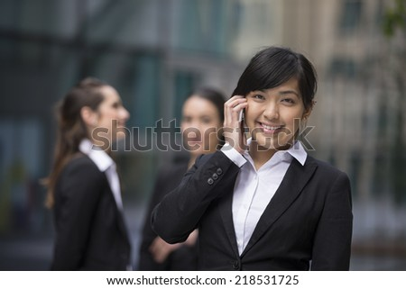 Portrait of a Asian businesswoman standing outside using mobile phone. Her colleagues are standing in the background. - stock photo