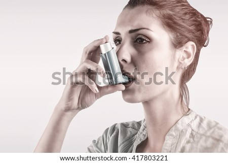 Portrait of a asthmatic woman against blue background - stock photo