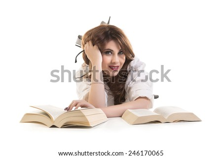 Portrait Of A Attractive Smiling Young Woman With Books Lying On Floor - stock photo