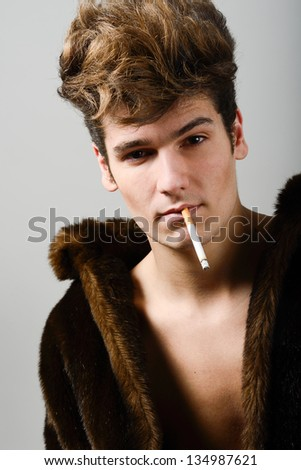 Portrait of a attractive young man wearing fur coat with modern hairstyle - stock photo
