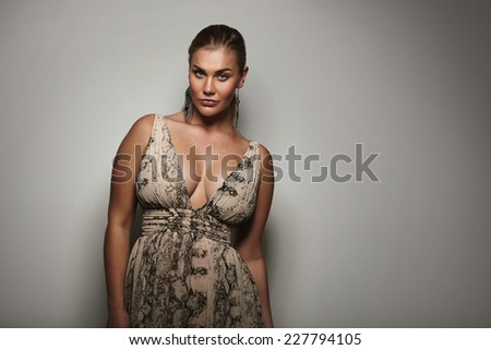 Portrait of a attractive young woman looking sensually at camera. Voluptuous female model posing a beautiful dress against grey background with copy space. - stock photo