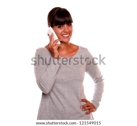 Portrait of a attractive young woman speaking on cellphone while is smiling at you on isolated background - stock photo