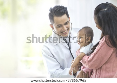 portrait of a baby being checked by a doctor using a stethoscope