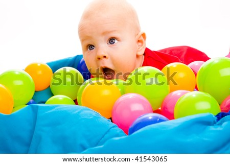 Portrait of a baby boy lying in basin with colorful balls - stock photo