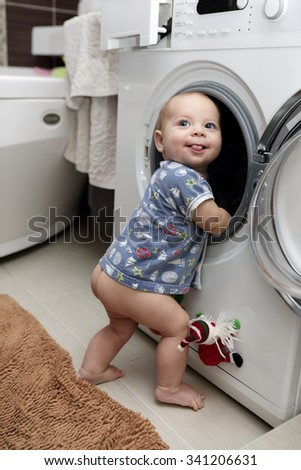 Portrait of a baby boy with washing machine