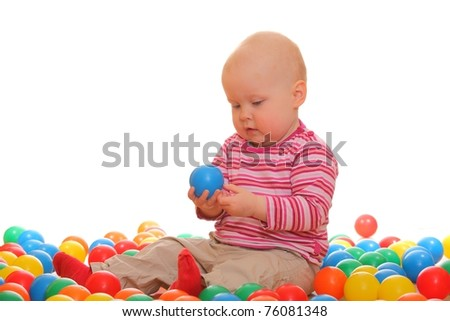 Portrait of a baby girl playing with lots of colored balls