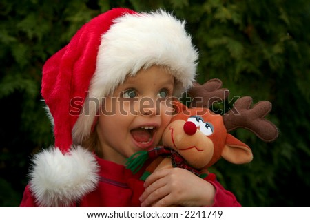 Portrait of a baby girl wearing Santa Claus hat with reindeer toy - stock photo