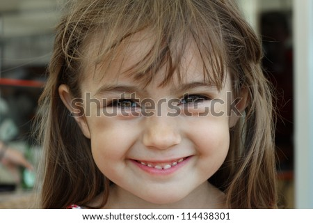 Portrait of a baby girl who smiles a toothy smile with a sparkle of happiness in her eyes. - stock photo