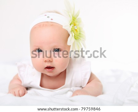 Portrait of a baby girl with a flower on her head on a white background - stock photo