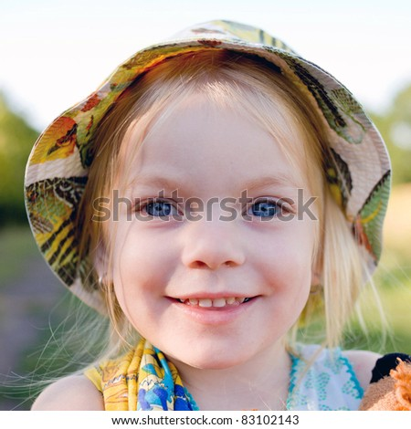 Portrait of a baby girl with blond hair and blue eyes wearing a hat closeup - stock photo