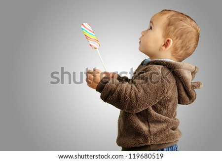 Portrait Of A Baby Holding Lollipop against a grey background