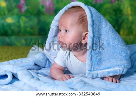 Portrait of a baby in a blue towel. On the green carpet. - stock photo