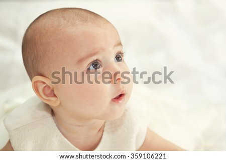 Portrait of a baby in baptismal clothing sitting on bed