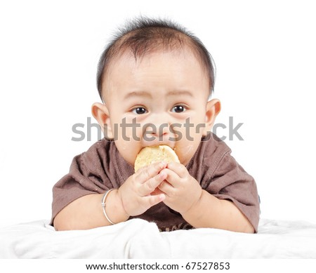 Portrait of a baby in funny expression holding and eating a biscuit - stock photo