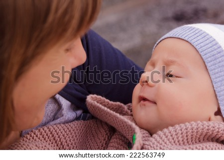 Portrait of a baby in the arms of mother - stock photo