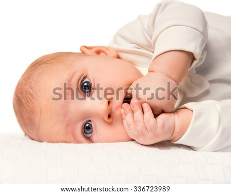 Portrait of a baby lying in bed at home - stock photo