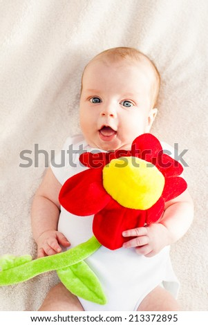 Portrait of a baby lying with flower - stock photo