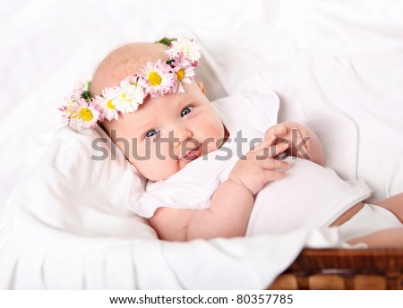 Portrait of a baby with a wreath of flowers on her head. - stock photo