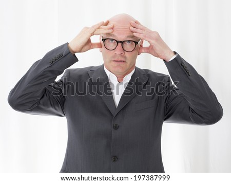 portrait of a bald-headed man in a suit with a headache - stock photo