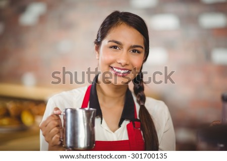 Portrait of a barista holding a milk jug at the coffee shop - stock photo