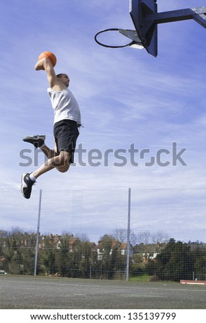 Portrait of a Basketball player about to Slam Dunk - stock photo
